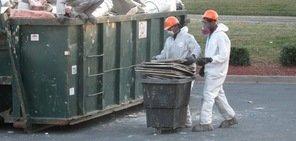 Water Damage Technicians Removing Debris To Street Dumpster